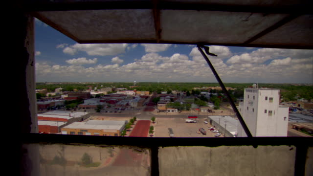 view of warehouses parking lot street commercial buildings cityscape through open window on cloudy day - kansas stock videos & royalty-free footage