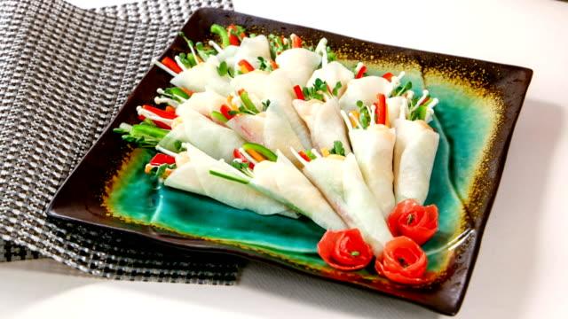 View of warped Mussammari (Korean pickled radish wraps) on a plate (Korean traditional dish)