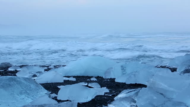 stockvideo's en b-roll-footage met ms pan view of washed glacier on jokulsa iceberg beach and snow mountain with ocean at mouth of jokulsarlon at dawn / iceland - meer dan 40 seconden