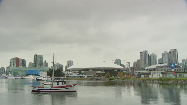 WS View of water and boat in front of BC place / Vancouver, British Columbia, Canada