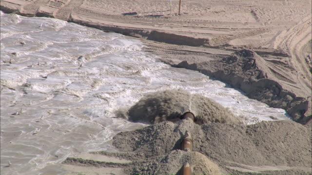 cu aerial view of water blowind through pipe in force / sylt, schleswig-holstein, germany - wasserverschmutzung stock-videos und b-roll-filmmaterial