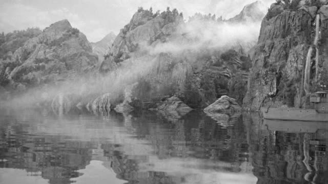 ws pan view of water to rugged mountain in background with two boats enter to town in the background fog at top of mountains - 50 seconds or greater stock videos & royalty-free footage