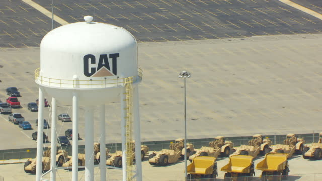 WS DS AERIAL POV View of water tower, cars and tractors parked in background at Caterpillar plant / Decatur, Illinois, United States