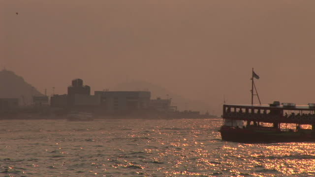 vidéos et rushes de view of water transportation at magic hour in hong kong china - aller tranquillement