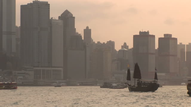 view of water transportation at magic hour in hong kong china - traghetto star video stock e b–roll
