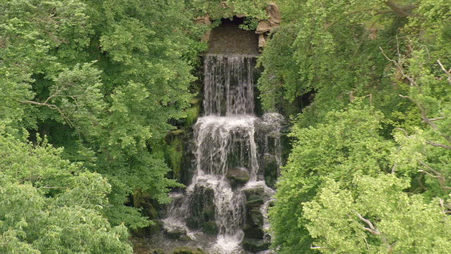 ms aerial zo view of waterfall in dense forest / wiltshire, united kingdom - ウィルトシャー州点の映像素材/bロール