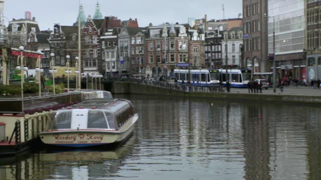 ws pan view of waterside restaurant over canal and people walking along street / amsterdam, holland - アムステルダム点の映像素材/bロール