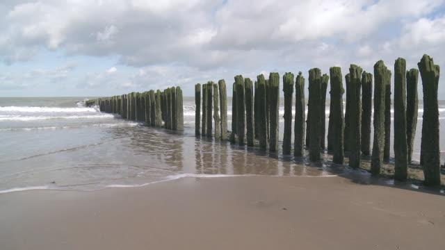 stockvideo's en b-roll-footage met ms view of wave breaker at beach of knokke / ostend, flanders, belgium - houten paal