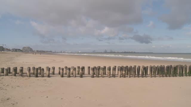 stockvideo's en b-roll-footage met ws view of wave breaker at beach of knokke with zeebrugge terminal / ostend, flanders, belgium - houten paal