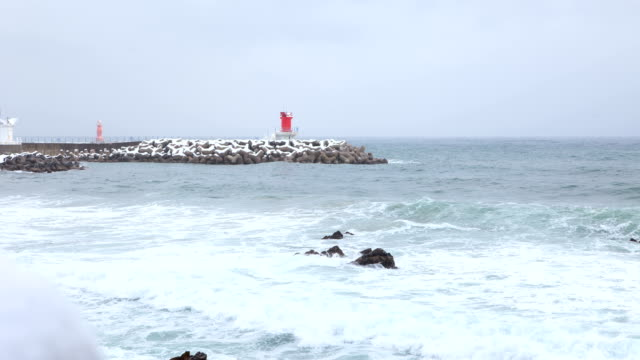 view of waves and lighthouse at mukho port in donghae city in winter - 突堤点の映像素材/bロール