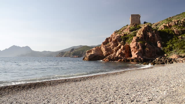 WS View of Waves at pebbles beach with genovese tower at rocky coast, UNESCO world heritage / Gulf of Porto, Corsica, France