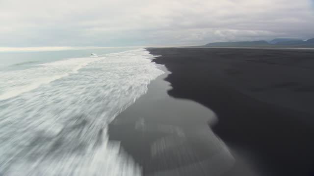 ws aerial zi pov view of waves crashing on skeidersandur coast / iceland - 海岸線点の映像素材/bロール