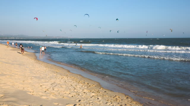 ws view of waves roll onto sandy beach with tourists and kitesurfers out at sea / mui ne, vietnam - vietnam meridionale video stock e b–roll