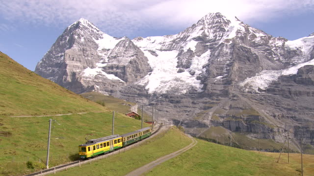 WS AERIAL View of Wengern Alp and wengernalp railway with impressive rock and ice walls of Eiger and Monch / Wengernalp, Bern, Switzerland