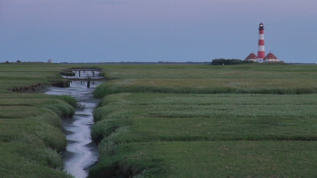 ws view of westerhever lighthouse from grass field at sunset and flowing river path, north frisian wadden sea / westerhever, schleswig holstein, germany - schleswig holstein stock videos & royalty-free footage