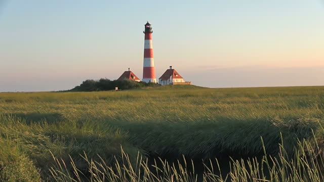 ws view of westerhever lighthouse from grass field at sunset, north frisian wadden sea / westerhever, schleswig holstein, germany - schleswig holstein stock videos & royalty-free footage