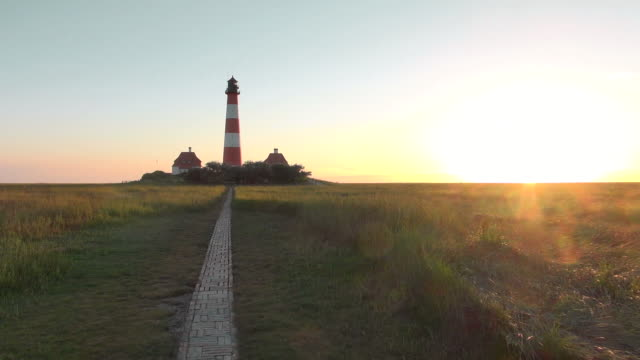 WS View of Westerhever lighthouse with walking trails from grass field at sunset, North Frisian Wadden Sea / Westerhever, Schleswig Holstein, Germany