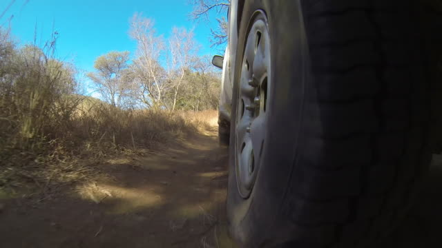 view of wheel of off-road vehicle travelling along dirt track. - 四輪駆動車点の映像素材/bロール