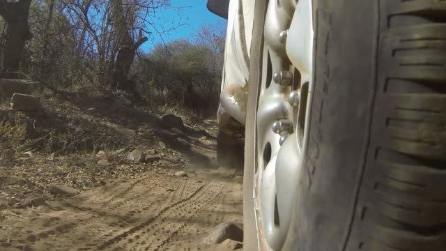 View of wheel of off-road vehicle travelling along dirt track.