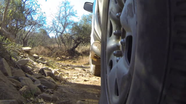 view of wheel of off-road vehicle travelling along dirt track. - tyre stock videos and b-roll footage