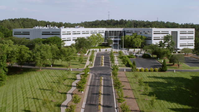 ws aerial pov view of white building at research triangle covered with tree / durham, north carolina, united states - centro di ricerca video stock e b–roll