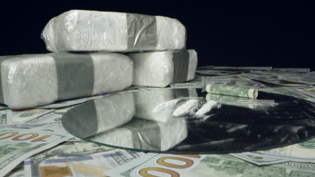 view of white powdered drugs on table top of money - snuff stock-videos und b-roll-filmmaterial