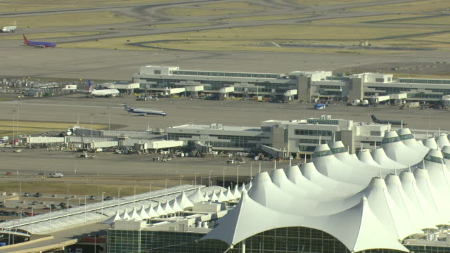 ms aerial view of white tent structures with peaks at denver international airport with airplanes moving on runways / denver, colorado, united states - colorado stock videos & royalty-free footage