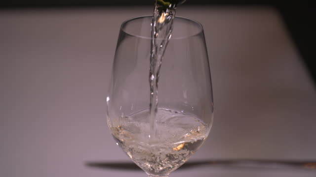 vídeos de stock e filmes b-roll de view of white wine being poured into a wine glass - copo