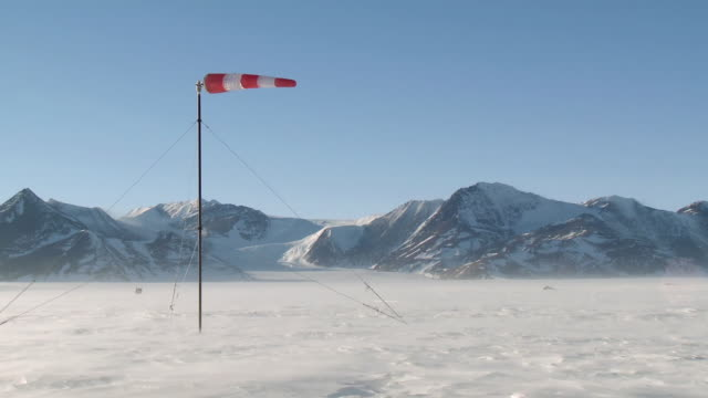 vídeos de stock, filmes e b-roll de ws view of wind sock in winds wept landscape of sparkling ice and snow with mountains / union glacier, heritage range, ellsworth mountains, antarctica  - biruta