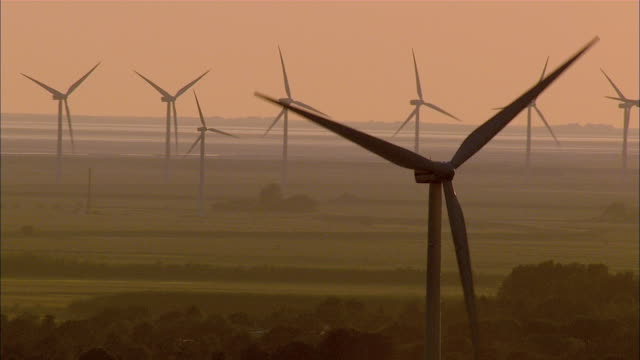 AERIAL WS View of wind turbine at sunset / Langeness, Schleswig-Holstein, Germany