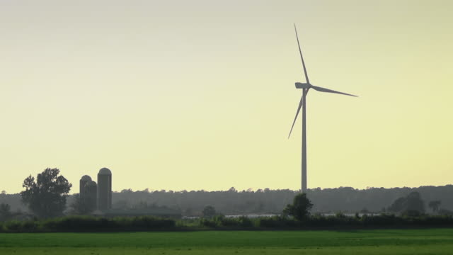 WS View of wind turbine located near farm field generating electricity at dusk / Garden, Michigan, United States