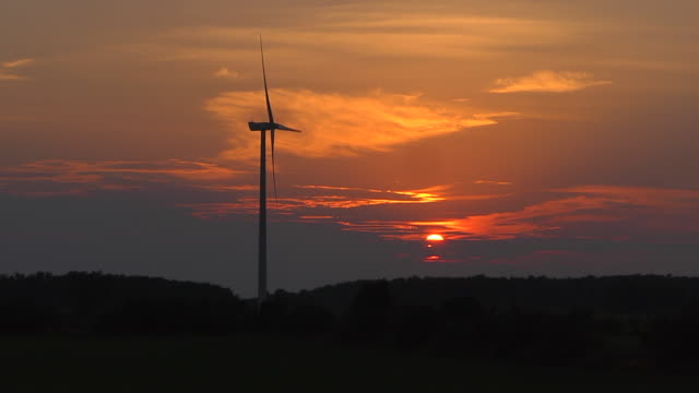vídeos y material grabado en eventos de stock de ws view of wind turbine located near farm field generating electricity as the sun sets / garden, michigan, united states  - michigan