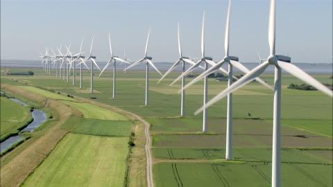aerial ms view of wind turbine on grass field/ niebuell+luebkekoog, schleswig-holstein, germany - 風力発電点の映像素材/bロール