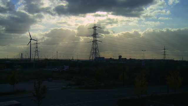 ws t/l view of wind turbine rotating, alongside electricity pylons / london, united kingdom  - 送電鉄塔点の映像素材/bロール