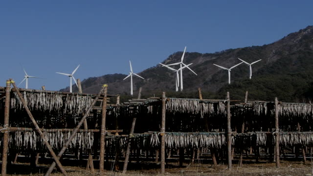 View of wind turbine spinning and Hanging dried fish at mountain