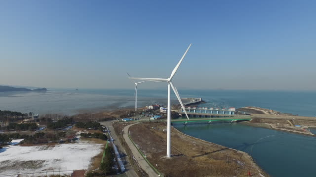 view of wind turbine spinning around at daebudo island - zoom out video stock e b–roll