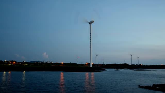 view of wind turbines at shinchang windmill coast in jeju island at night - naturwunder stock-videos und b-roll-filmmaterial