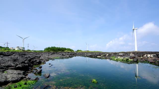 view of wind turbines at shinchang windmill coast in jeju island - 自然奇觀 個影片檔及 b 捲影像