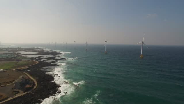 view of wind turbines standing at a wind farm and seascape in seogwipo, jeju island - turbine stock videos & royalty-free footage