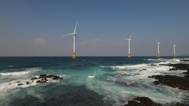 view of wind turbines standing at a wind farm and seascape in seogwipo, jeju island - wind turbine stock videos & royalty-free footage