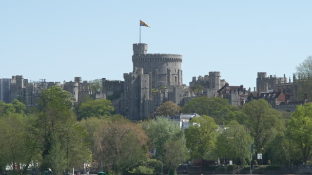 view of windsor castle where queen elizabeth is self-isolating during the coronavirus pandemic. windsor and eton residents, in the foreground, enjoy... - ウィンザー城点の映像素材/bロール