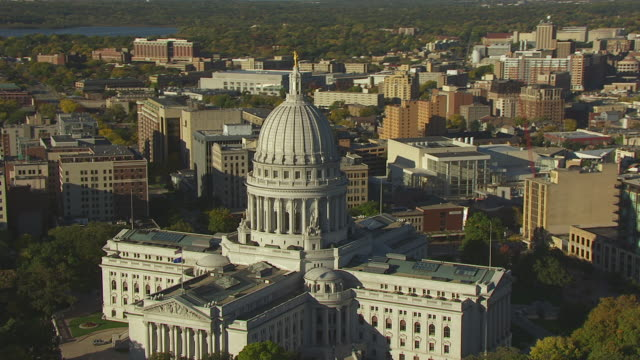 WS AERIAL POV View of Wisconsin state capital building with cityscape / Madison, Wisconsin, United States