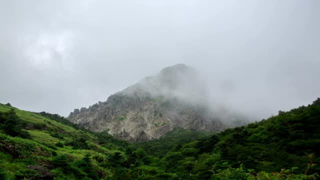 vídeos de stock, filmes e b-roll de view of witseoreum (mountain hill) with fog at hallasan mountain (unesco world heritage) in jeju island - ponto de referência natural