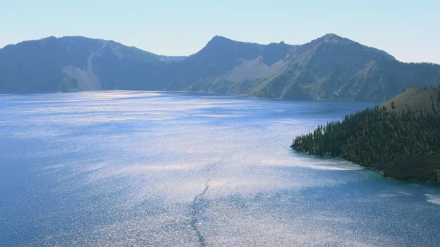 ws pan view of wizard island at illuminated surface of crater lake by sun / klamath county, oregon, united states - crater lake oregon stock videos & royalty-free footage