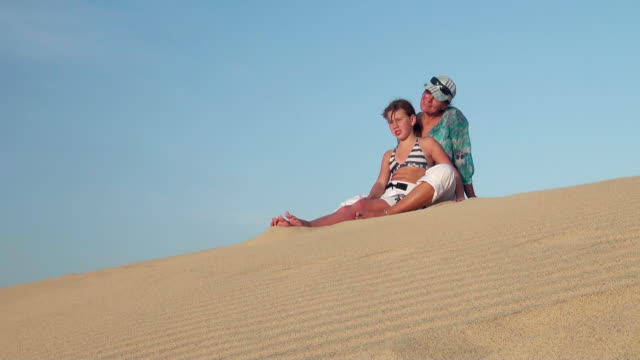 ms view of woman and her girl seating on dune at beach near santa maria / santa maria, sal, cape verde - verde color stock videos & royalty-free footage
