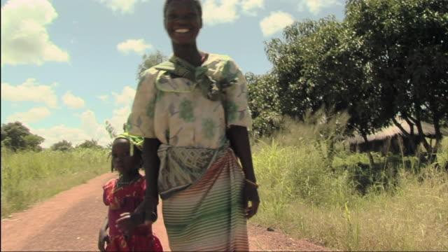 vídeos de stock e filmes b-roll de ms pov view of woman carrying child and singing / mozambique - moçambique