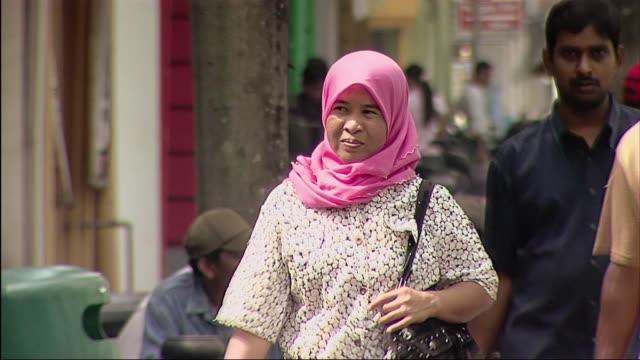 ms view of woman in pink headscarf on street / malaysia - only mid adult women stock videos & royalty-free footage