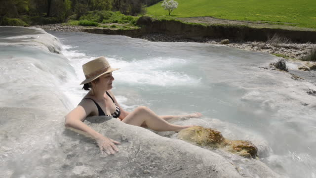 ws view of woman relaxing in hot spring, thermal pools of sulphurous water / saturnia, tuscany, italy - natürliches thermalbecken stock-videos und b-roll-filmmaterial