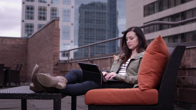 View of woman relaxing on roof top typing on laptop running fingers through hair.