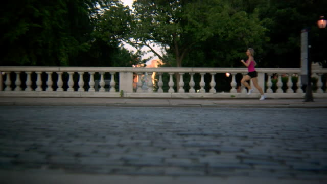 MS SLO MO View of Woman Running in city in front of  bridge / Baltimore, Maryland, USA
